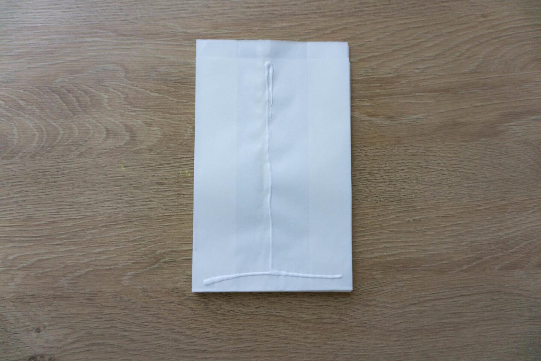 Mit Bastelkleber ein verkehrtes T auf die Tüten machen